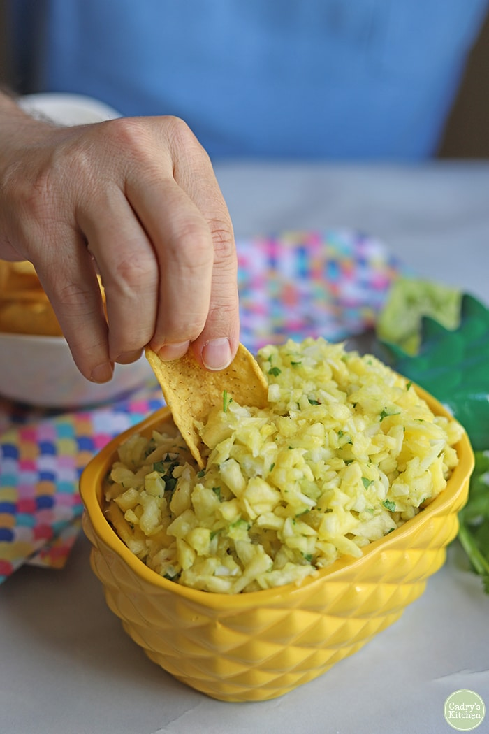 Hand dipping chip into pineapple salsa.
