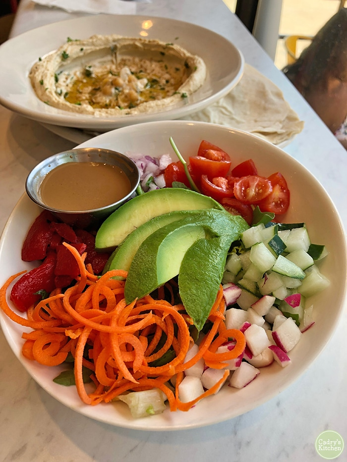 Rainbow salad and hummus on counter.