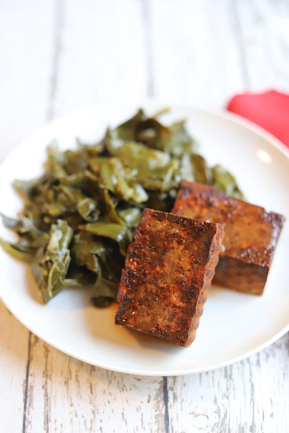 Smoked tofu and collard greens on plate.
