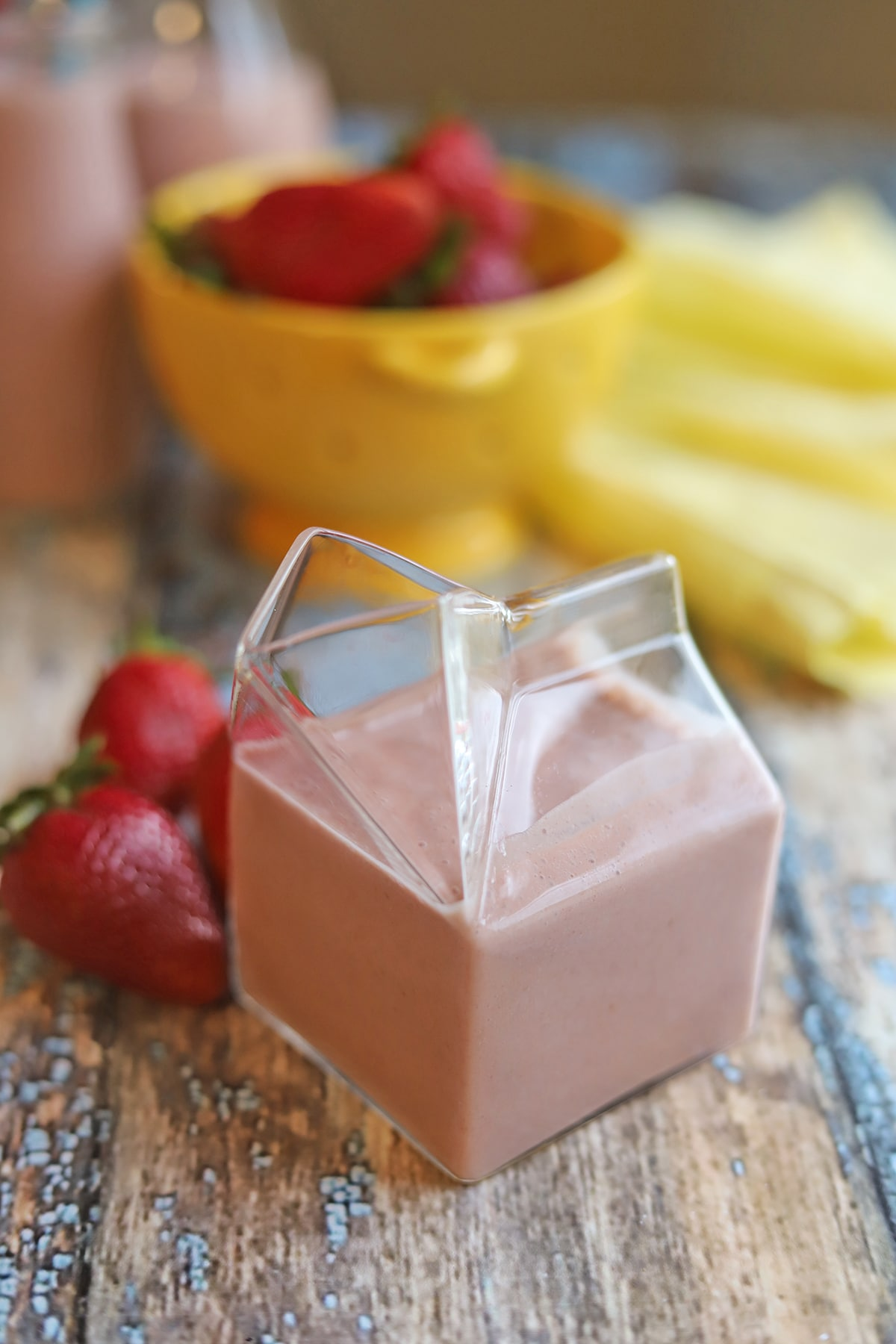 Old school style glass milk container filled with strawberry milk.