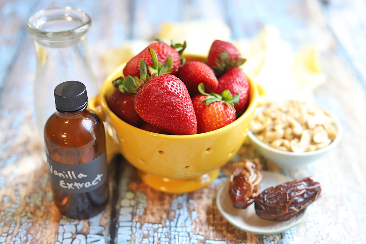 Ingredients for strawberry milk: strawberries, water, vanilla extract, dates, and cashews.