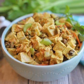 Bowl of curried tofu salad on table.