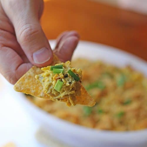 Hand dipping tortilla chip with vegan spinach artichoke dip.