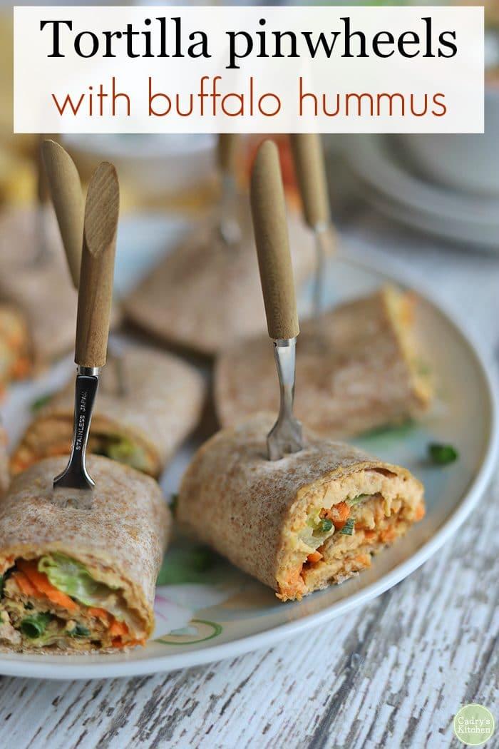 Text: Tortilla pinwheels with buffalo hummus. Tortilla rollups on plate with hummus filling.