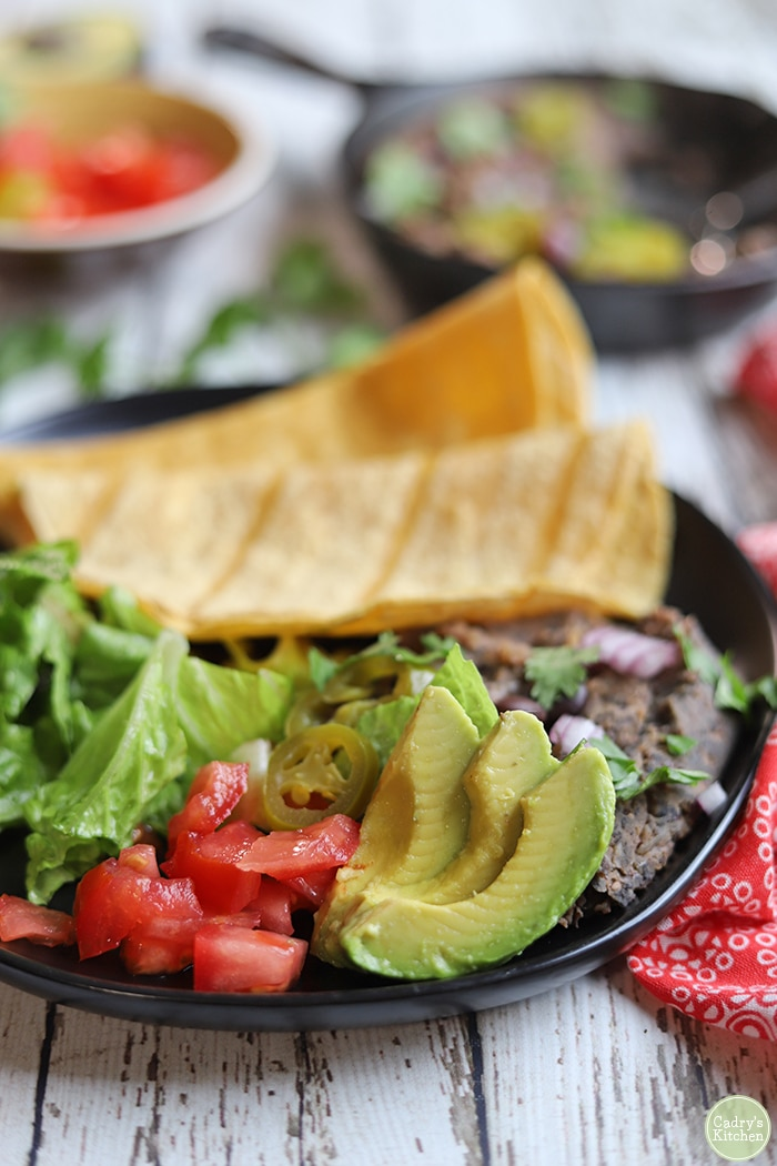Plate with avocado, tomatoes, lettuce, refried black beans, and corn tortillas.