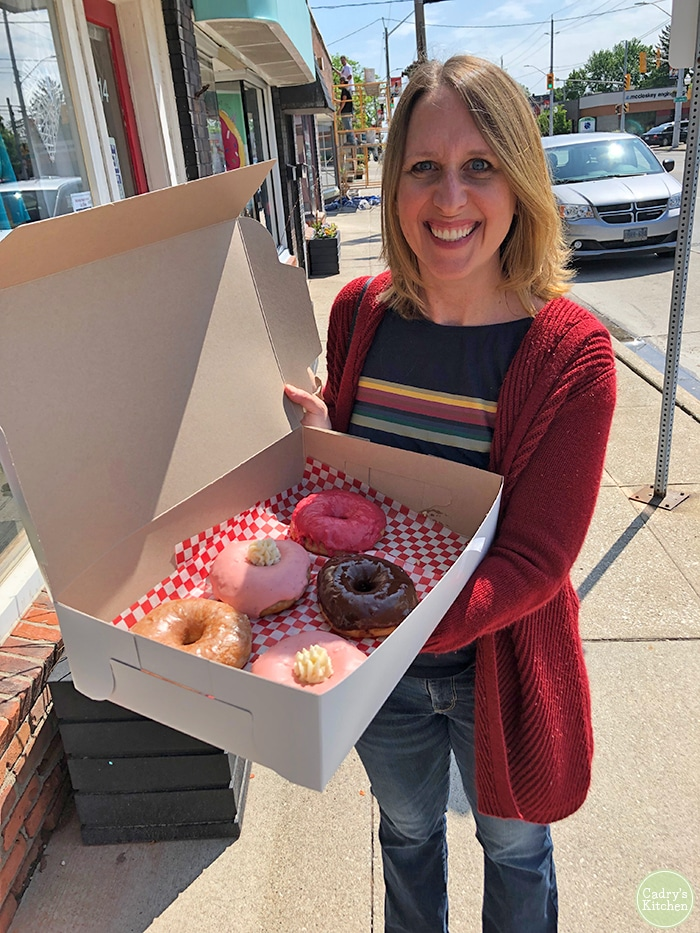 Cadry holding a box of vegan donuts in front of Plant Joy.