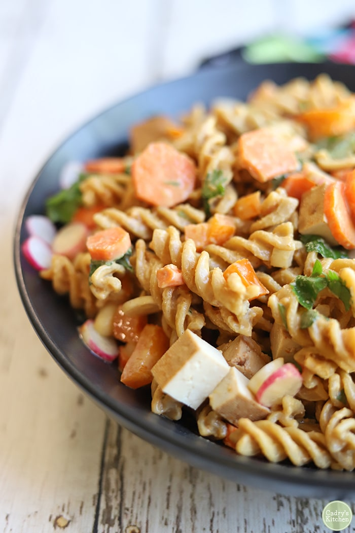 Close up cold noodle salad with tofu, carrots, cilantro, radishes, and pasta drenched in peanut sauce.