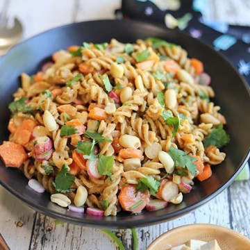 Cold noodle salad with peanut sauce in bowl by black napkin.