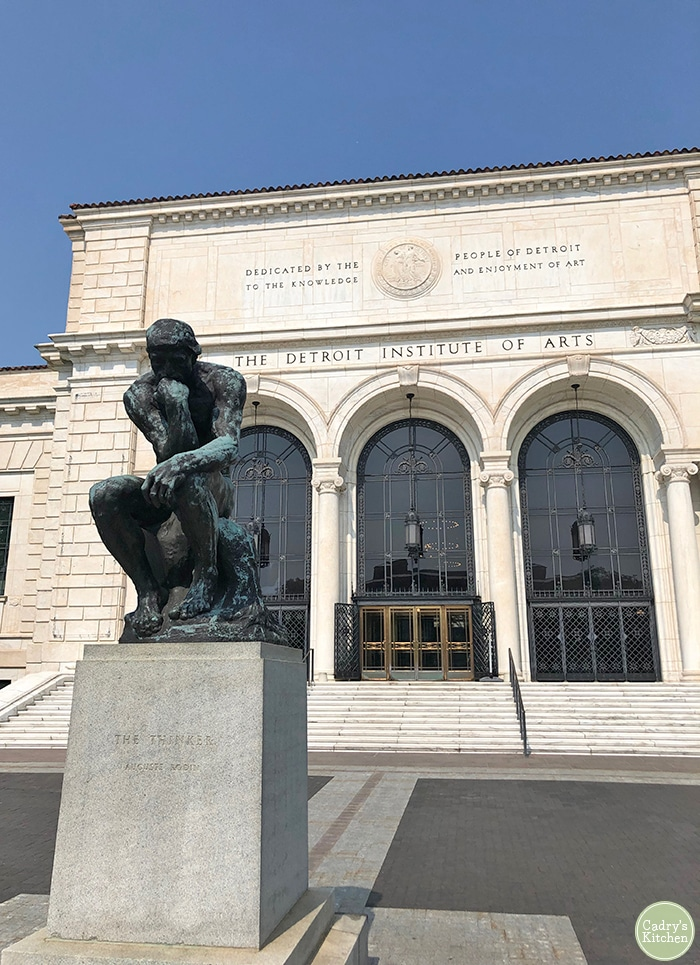 Exterior of the Detroit Institute of Arts with the Thinker in front of it.