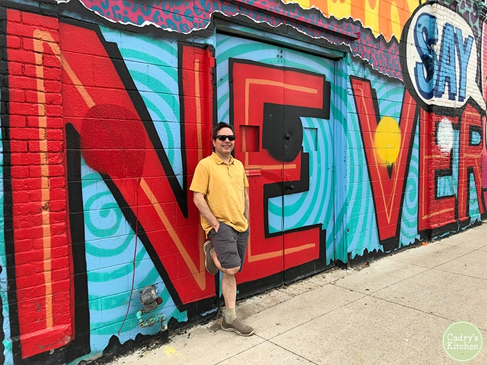 David standing in front of a mural near the Eastern Market.