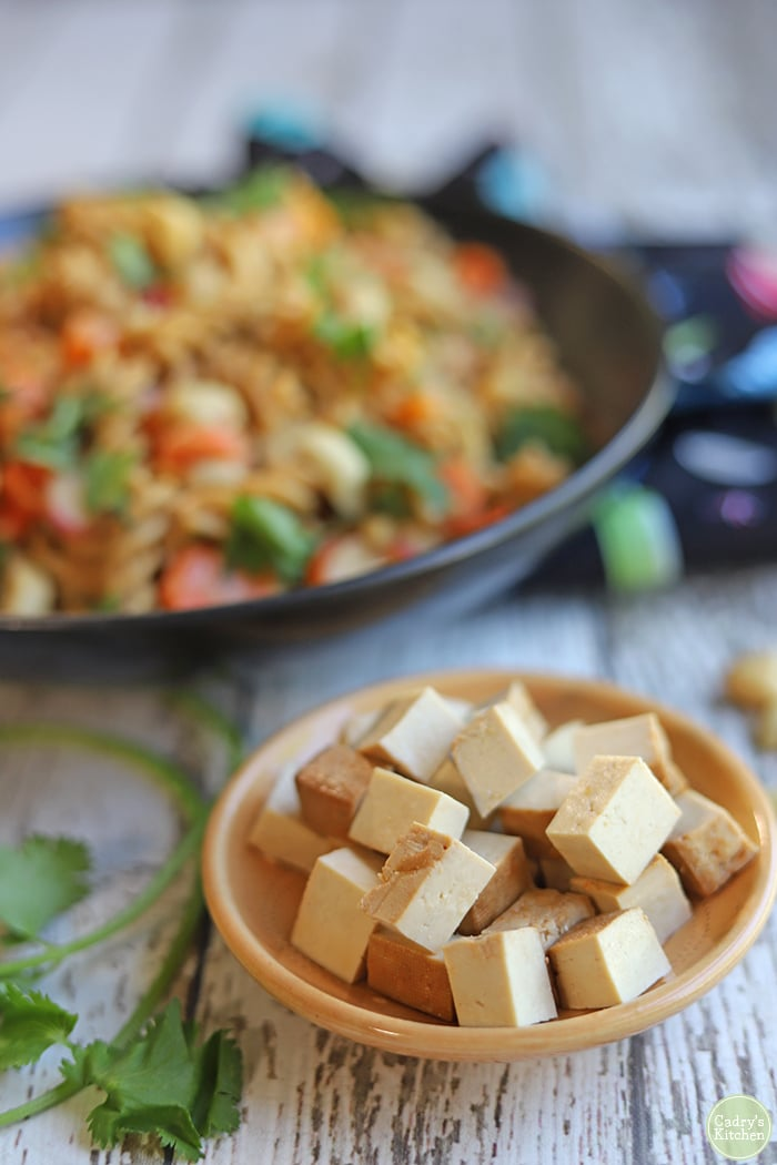 Cubed tofu in small dish with noodle salad in background.