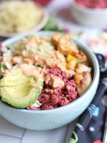 Close-up nourish bowl with jackfruit corned beef, sauerkraut, vegan Thousand Island dressing, and potatoes.