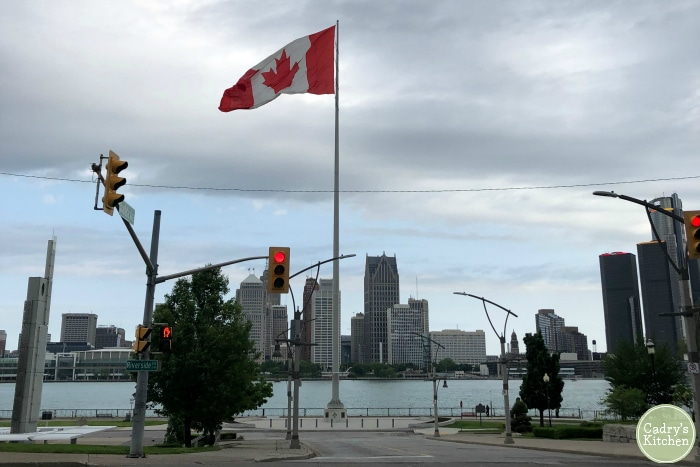 Windsor Ontario border along Detroit River with Canadian flag in foreground.