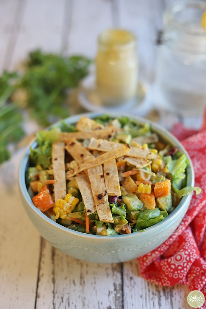 Southwestern salad in bowl with tortilla strips on top.