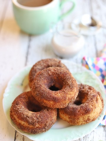 Platter of baked vegan donuts. Coffee & non-dairy milk in background.