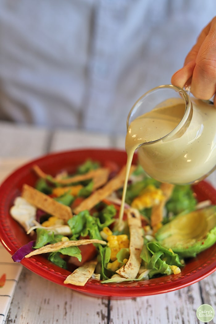 Tiny pitcher of creamy cashew salad dressing getting poured onto salad.