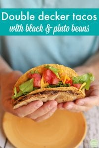 Text: Double decker tacos with black and pinto beans. Hands holding taco.