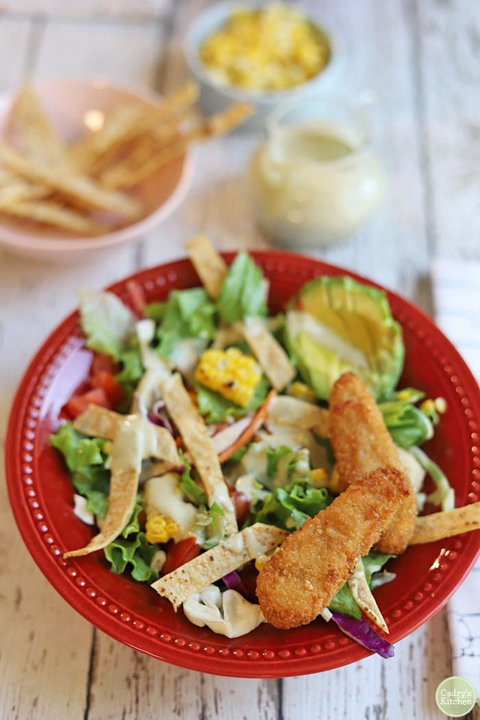 Lettuce, tortillas, corn, and avocado in red bowl with Trader Joe's chickenless strips on top.
