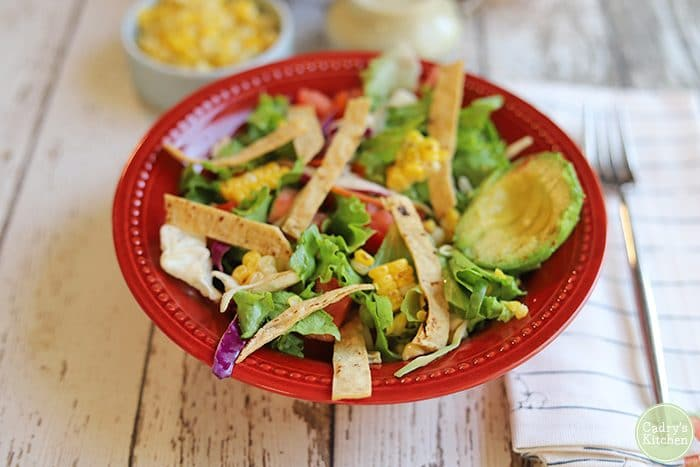 Bowl of southwest salad with crispy corn tortilla chips, and avocado.
