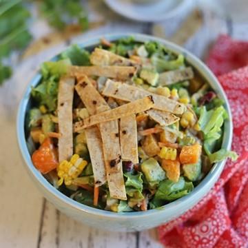 Crunchy tortilla strips on a salad in bowl.
