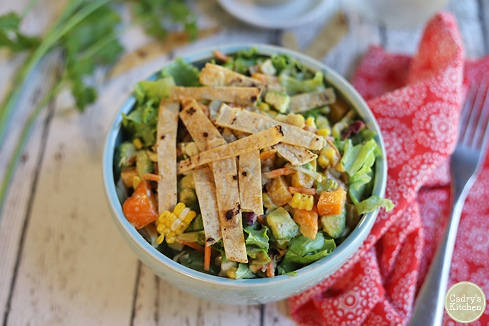 Crunchy tortilla strips on a salad in bowl.