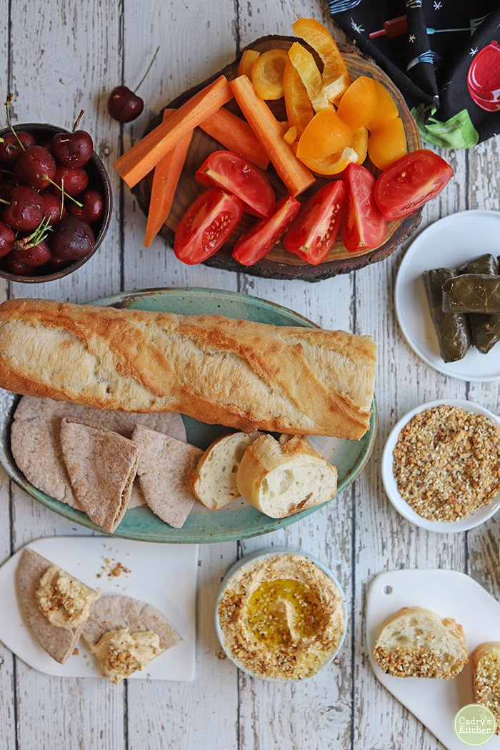 Overhead bread with oil, dukkah, hummus, fruits, and vegetables.