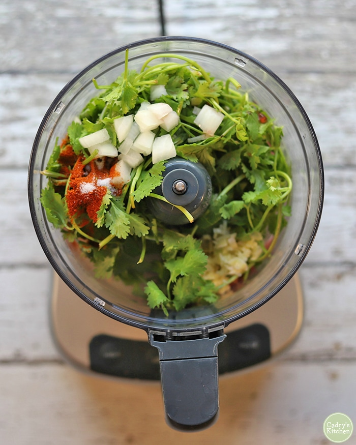 Overhead food processor with cilantro, onions, paprika, garlic, oil, and vinegar.