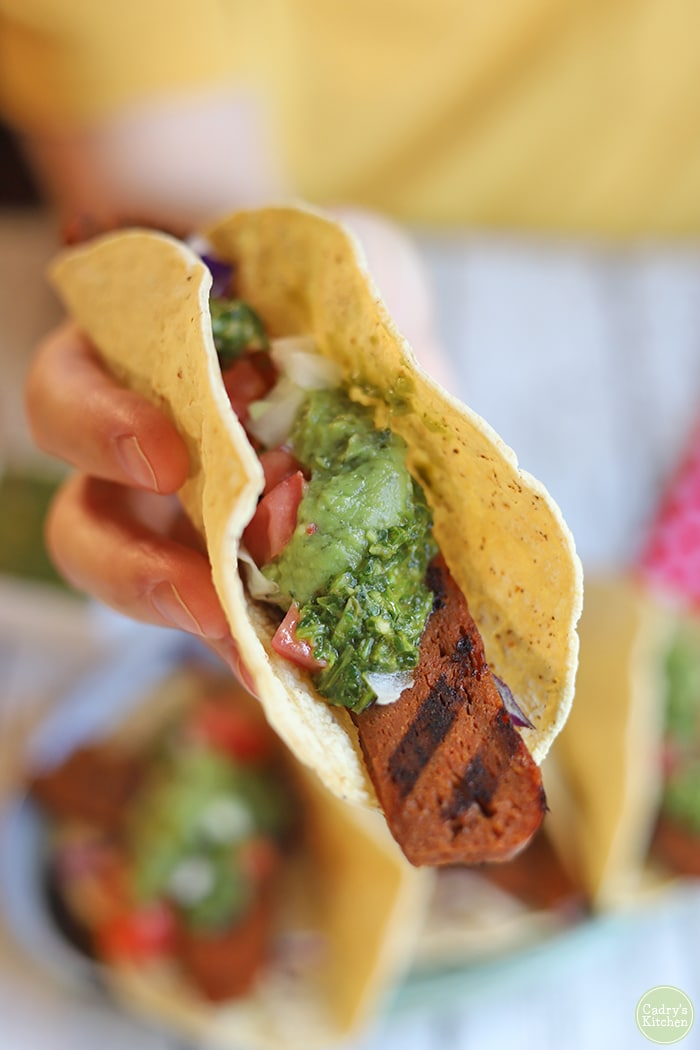 Hand holding vegan steak taco with guacamole and cilantro chimichurri sauce.