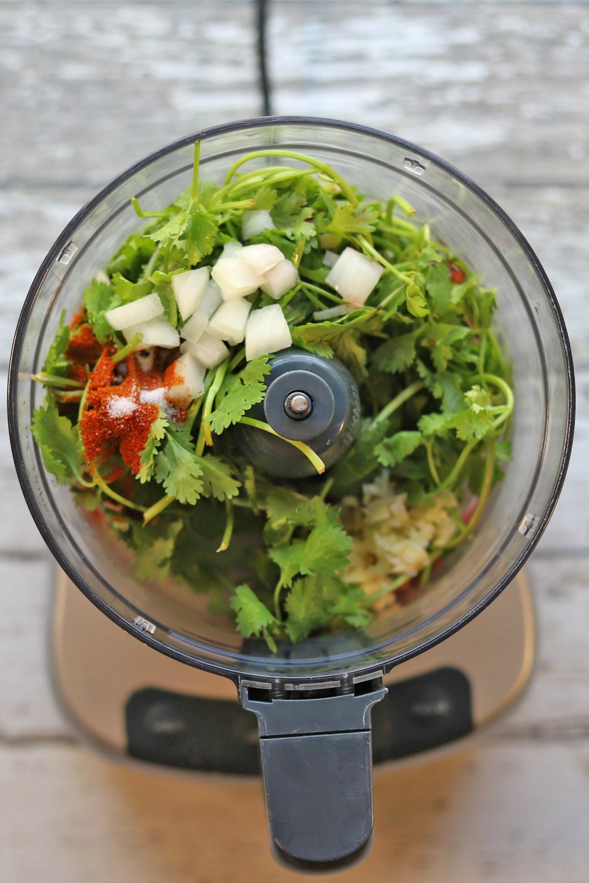 Overhead food processor with cilantro, onions, spices, garlic, and vinegar.