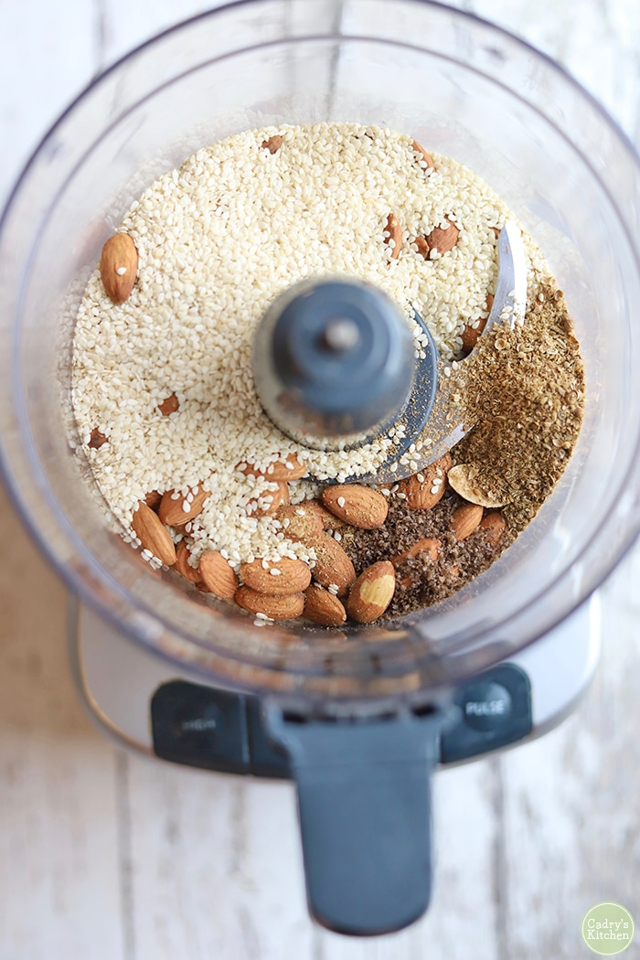 Almonds, spices, and sesame seeds in food processor.