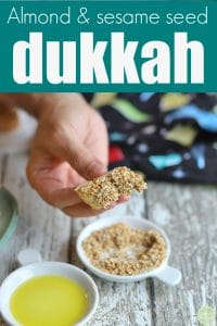 Text: Almond & sesame seed dukkah. Hand holding bread that's dipped in dukkah.