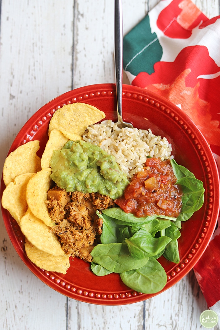 Overhead burrito bowl with shredded jackfruit chicken, rice, spinach, guacamole, and salsa.