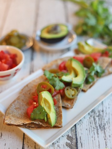 Wedges of a vegan quesadilla on plate with avocado, tomatoes, and jalapeno pepper slices.