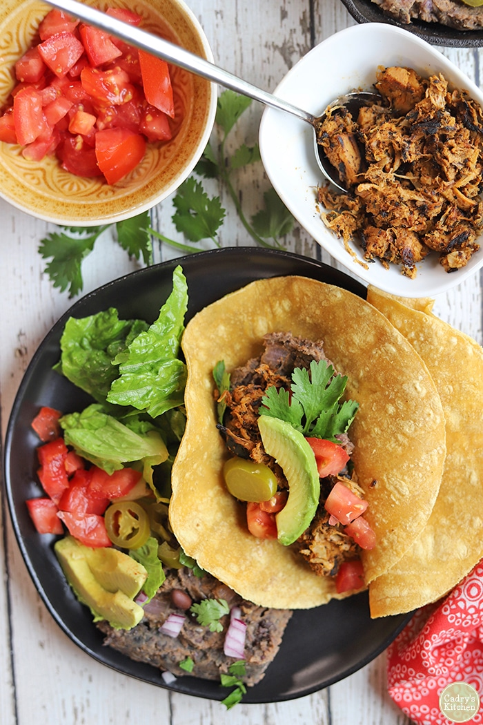 Overhead shredded jackfruit chicken tacos with avocado and tomatoes.
