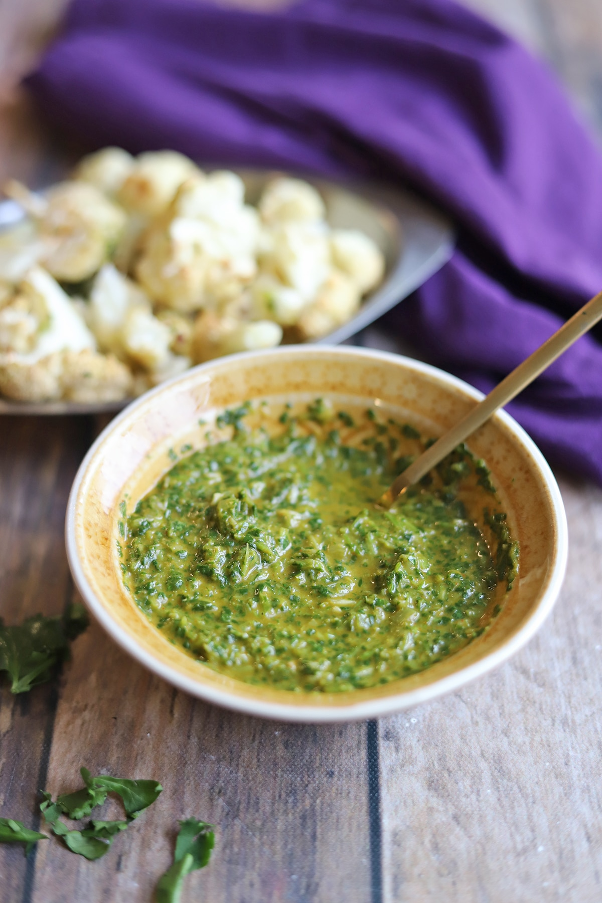 Bowl of chimichurri sauce by cauliflower florets.