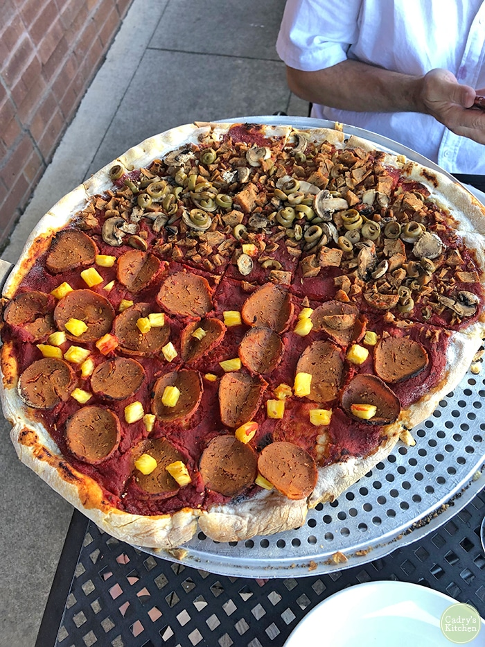 Pizza with vegan pepperoni & pineapple on one side, sausage, olives, and onions on the other.
