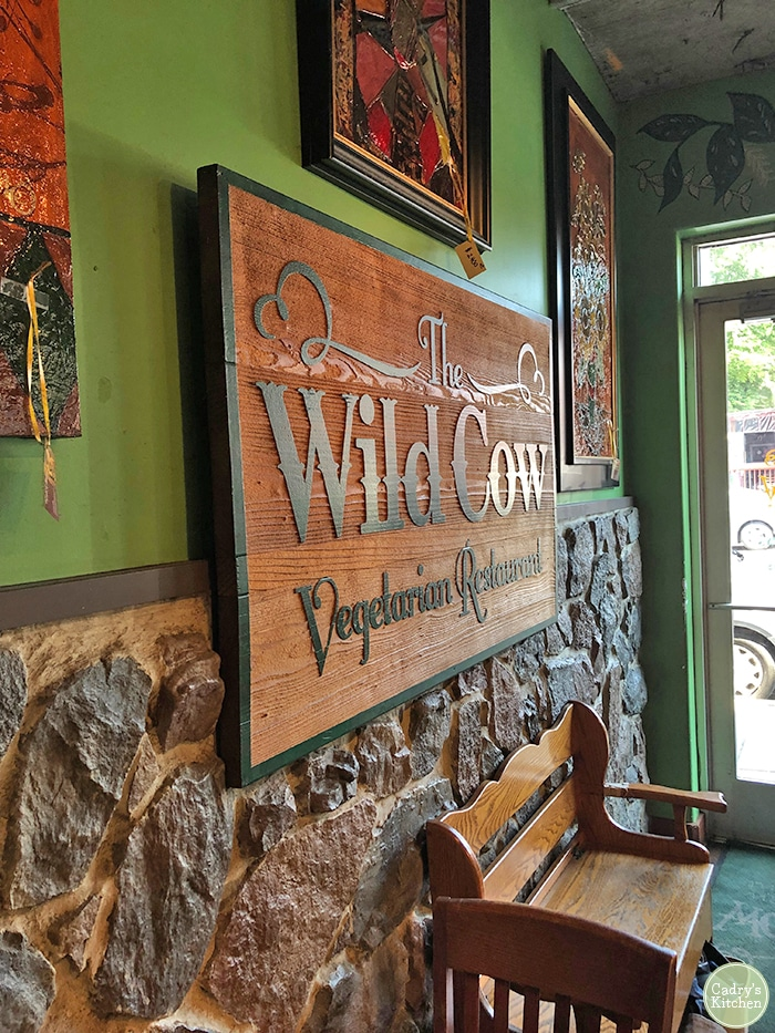 """Wooden sign that says, """"The Wild Cow vegetarian restaurant."""""""