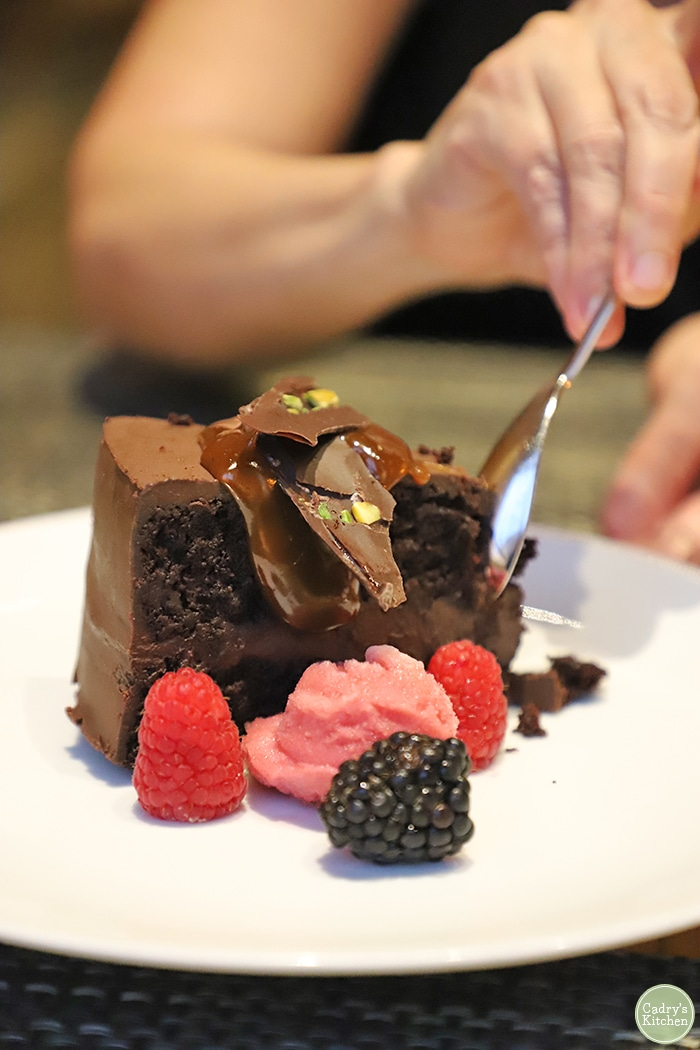 Spoon digging in to chocolate cake with fruit sorbet for a Minneapolis date night..
