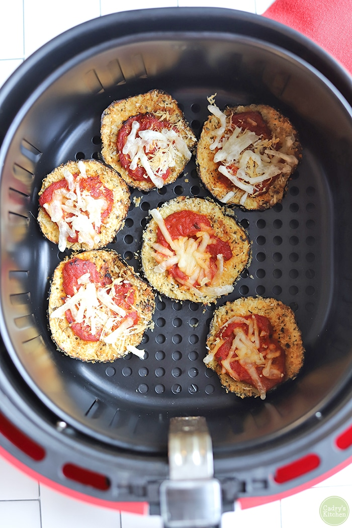 Breaded eggplant slices with marinara and non-dairy cheese in air fryer basket.
