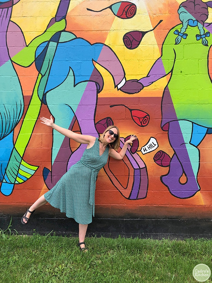 Cadry posing in front of a mural in Mason City Iowa.