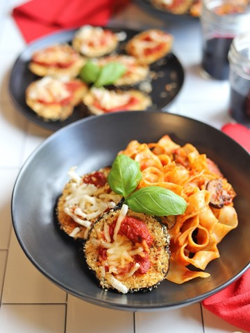 Bowls of pasta with eggplant parmesan slices.