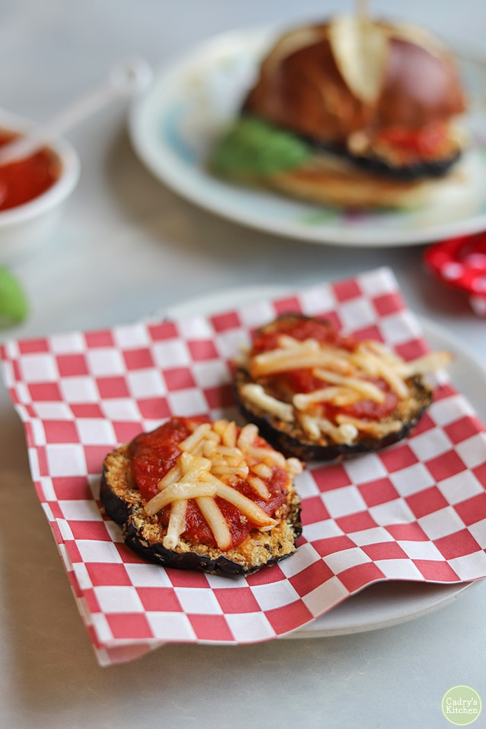 Slices of eggplant parmesan on checkered paper.