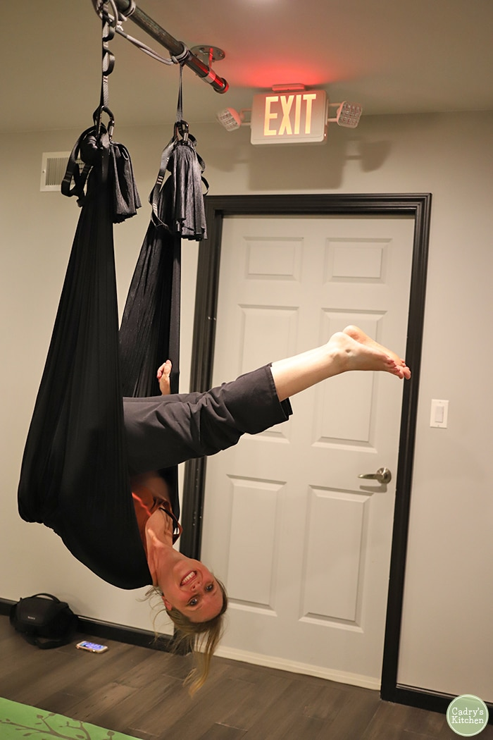 Cadry hanging upside down doing aerial yoga.