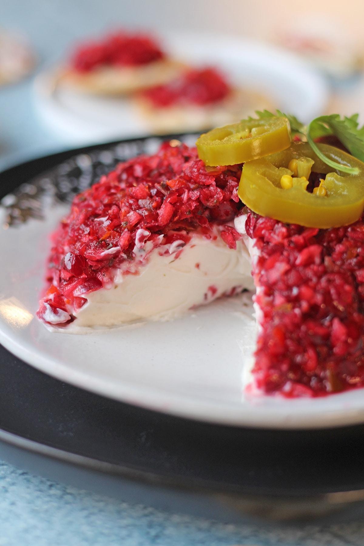 Cranberry salsa over vegan cream cheese on plate.