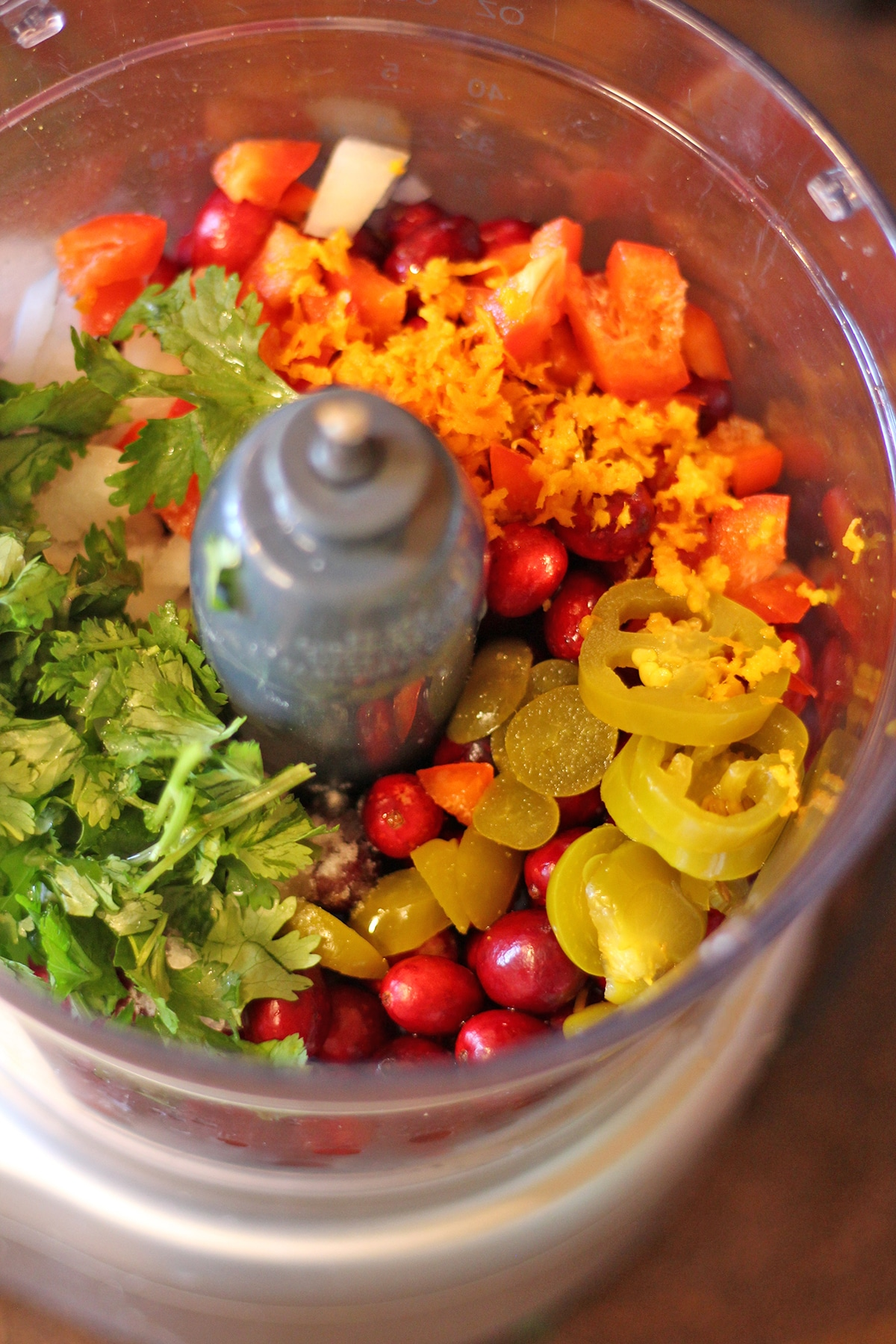 Food processor with cranberries, jalapenos, bell pepper, cilantro, and orange zest.
