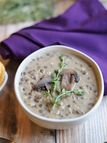 Mushroom soup with lentils and brown rice in bowl topped with fresh thyme.