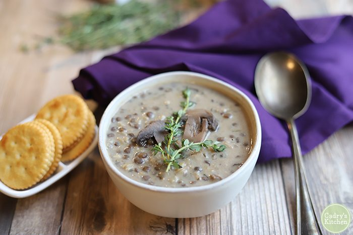 Vegan mushroom soup in bowl with crackers, spoon, and purple napkin.