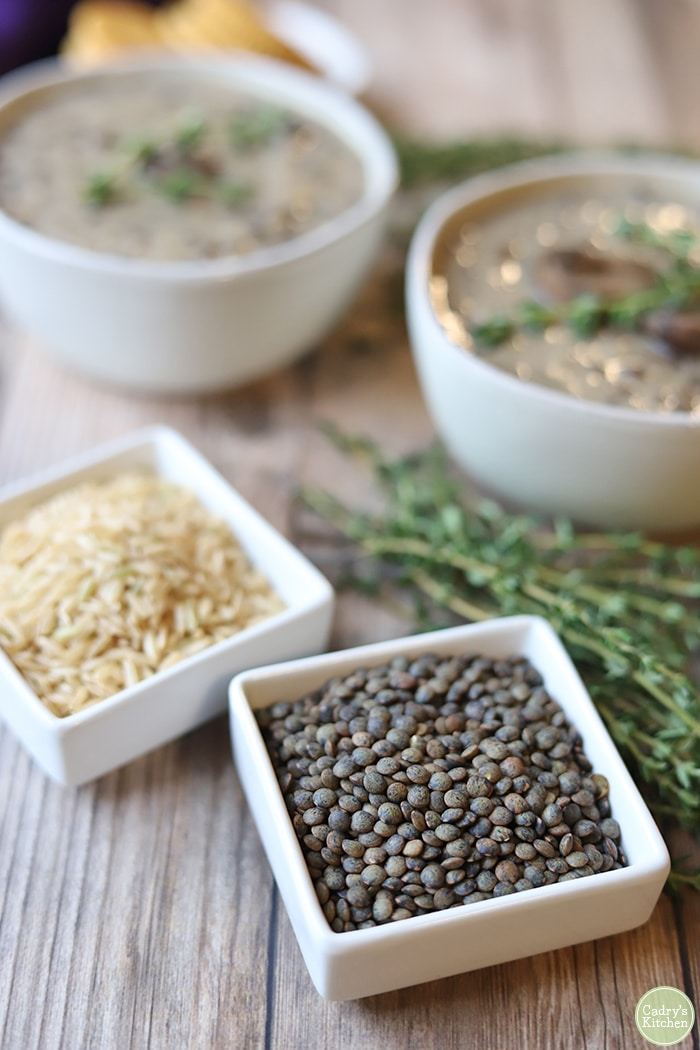 Lentils and brown rice by bowls of soup.