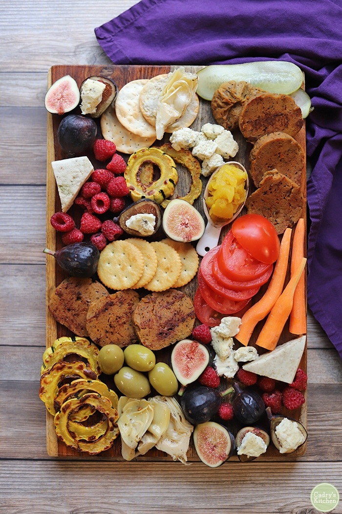 Vegan charcuterie board with olives, seitan, non-dairy cheese, fruits, and vegetables.
