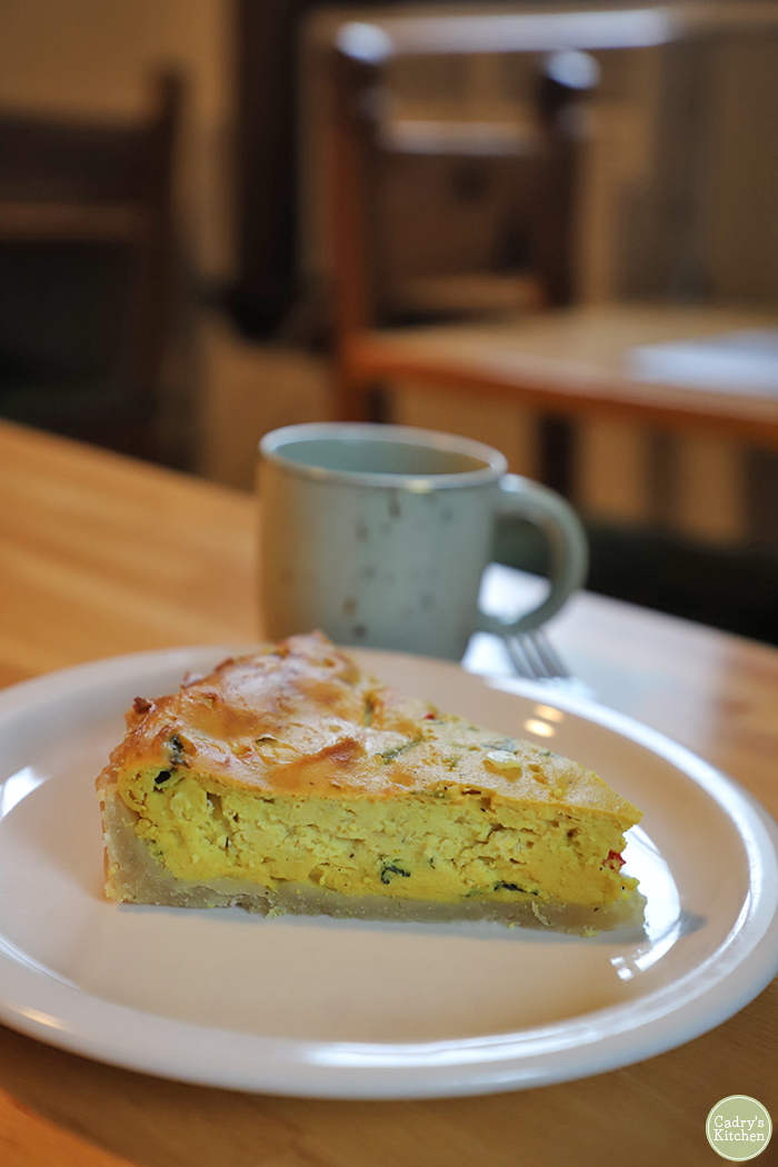 Vegan quiche on plate with coffee at Vegan East.